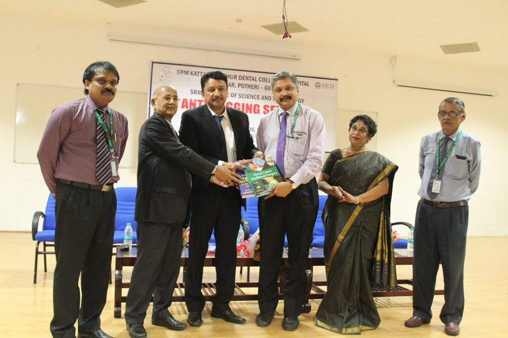 Dr Balaji presenting the books Clinical Cranio-Maxillofacial Surgery and Textbook of Oral and Maxillofacial Surgery authored by him to Dr. N Vivek