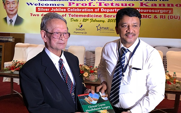"Dr SM Balaji presenting his textbook ""Clinical Cranio-Maxillofacial Surgery"" to Prof Tetsuo Kanno"